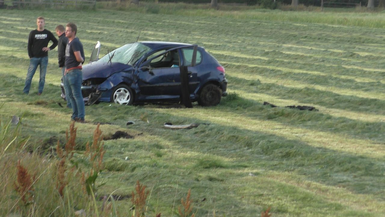 Auto crasht en slaat over de kop beland in weiland