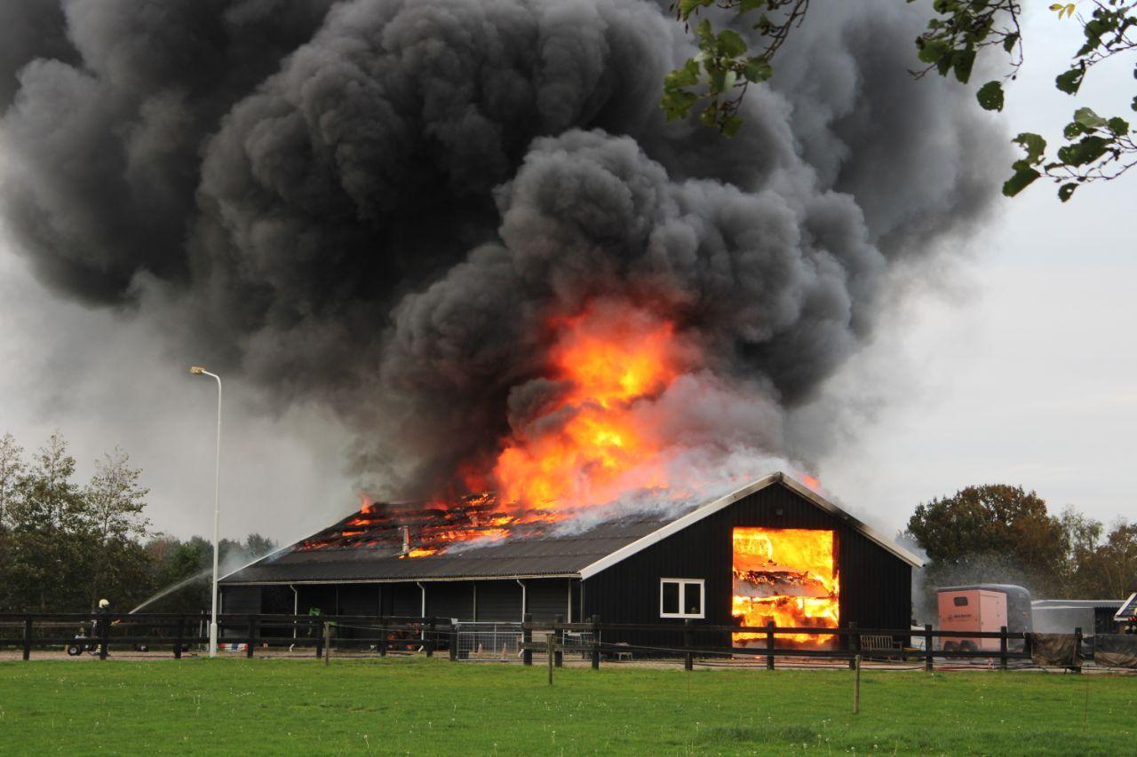 uitslaande brand in een loods met vrachtwagens