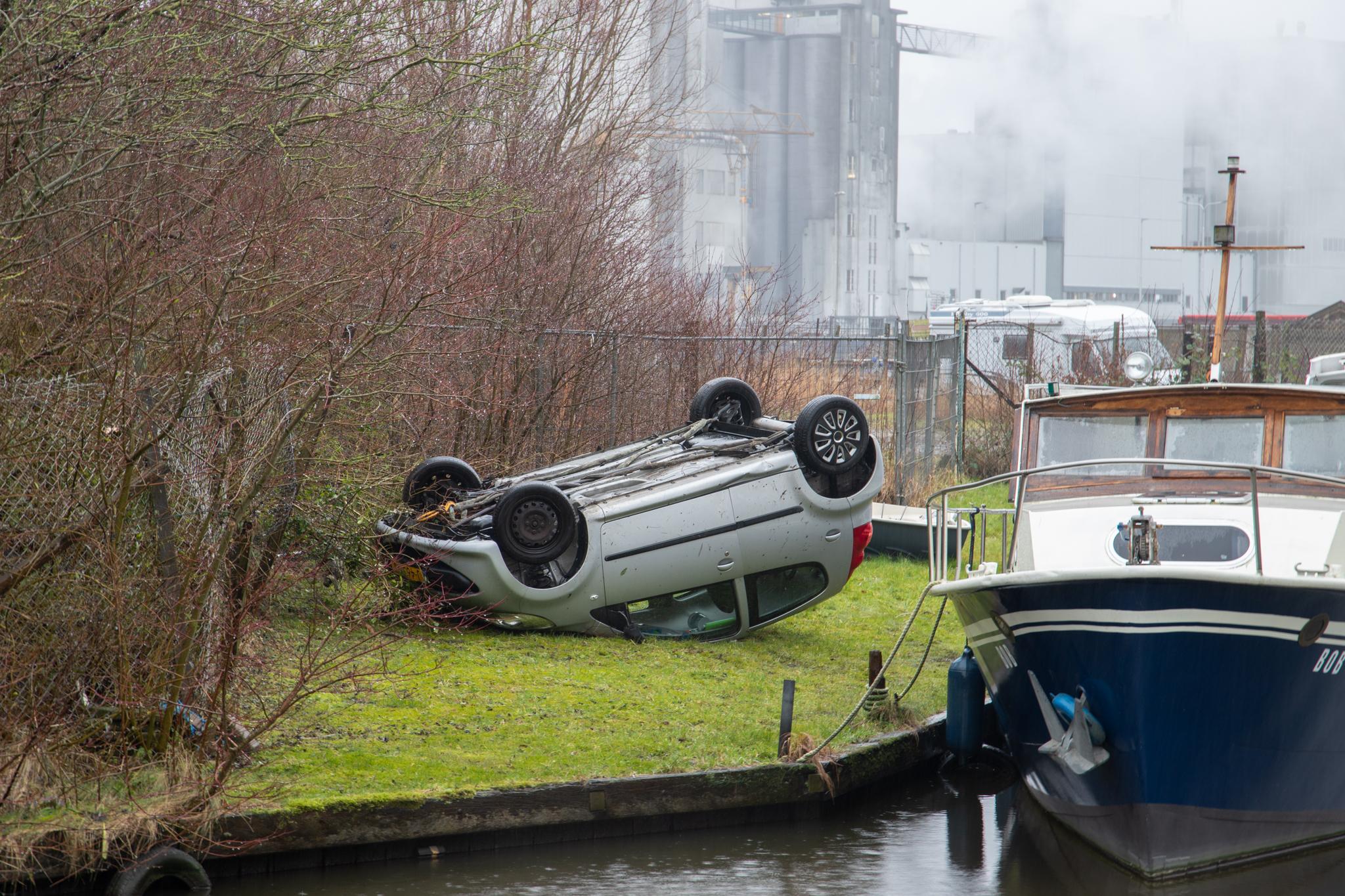 Bestuurder raakt van de talud en belandt op de kop langs de kanaalweg in Leeuwarden